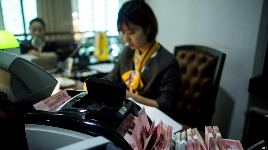 2018年8月8日在上海的一家银行,员工使用点钞机点算100元(相当于14.6美元)的钞票。