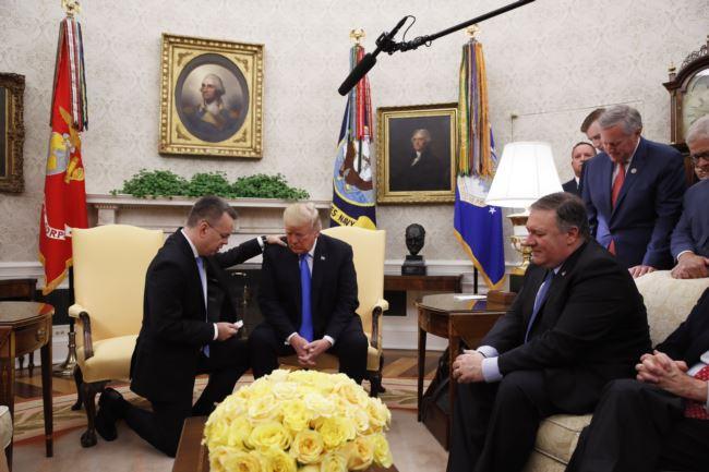 美国总统特朗普在白宫的总统办公室和美国牧师安德鲁·布伦森一起祈祷(2018年10月13日)。