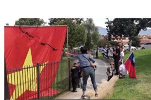 一名抱小孩的妇女向五星旗泼墨